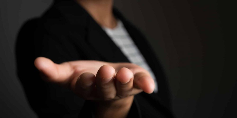 vecteezy_business-woman-s-hand-showing-blank-area-for-sign-or-copyspace-isolated-on-black-background_2060497_reduced